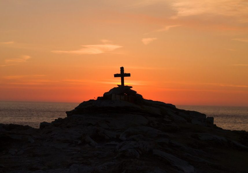 Cross on a hill with sunset in the background